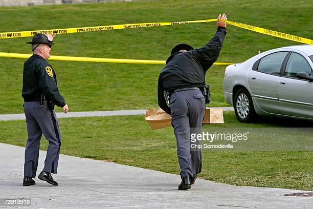 Virginia State police carry bags of evidence underneath crime scene tape outside Norris Hall after reports of a security alert on the campus of...
