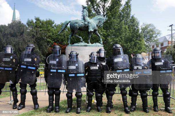 Virginia State Police in riot gear stand in front of the statue of General Robert E Lee before forcing white nationalists neoNazis and members of the...
