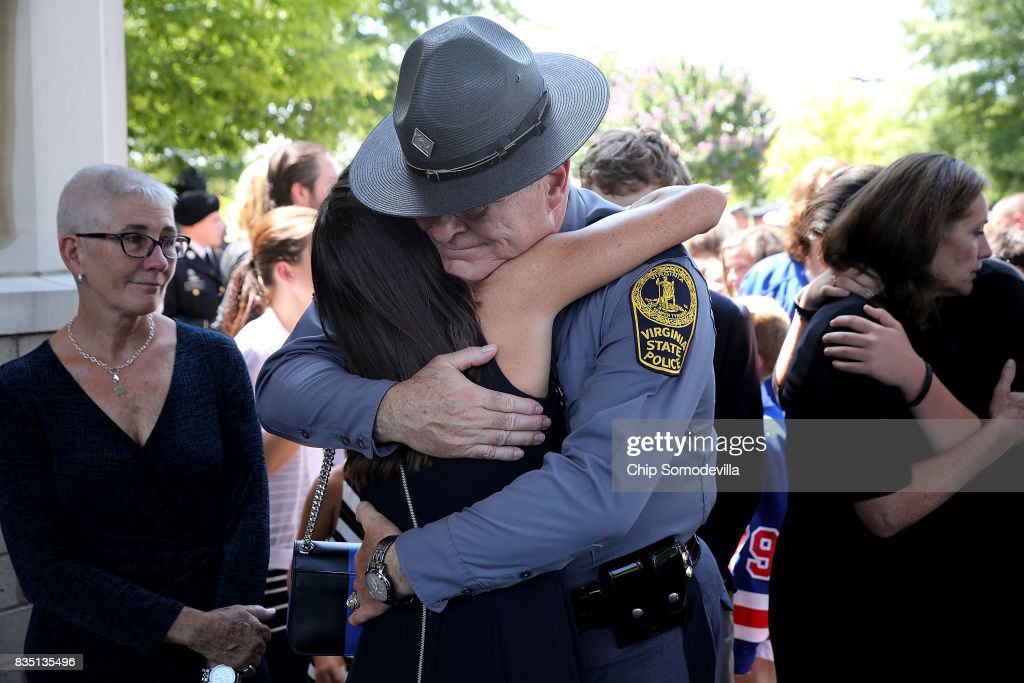Virginia State Police Superintendent Colonel Steven Flaherty gets a hug following the funeral for Trooper-Pilot Berke M.M. Bates at Saint Paul's Baptist Church August 18, 2017 in Richmond, Virginia. Bates and Lieutenant Pilot Jay Cullen were killed when their Bell 407 helicopter crashed into a wooded area while they were monitoring the civil unrest during the white supremacy 'Unite the Right' rally August 12 in Charlottesville, VA.