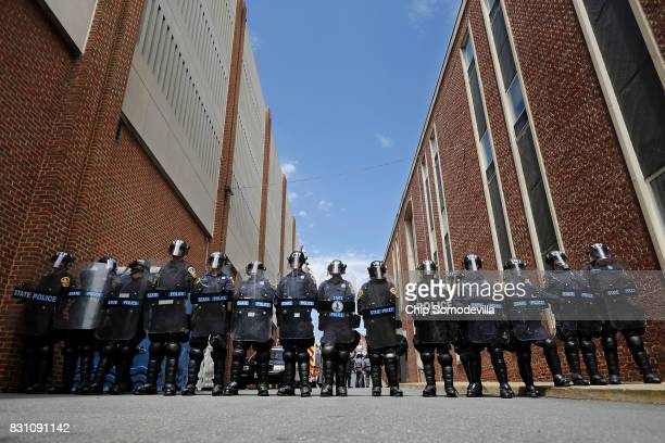 Virginia State Police wear body armor and use riot shields while forming a cordon around police headquarters where altright blogger Jason Kessler was...