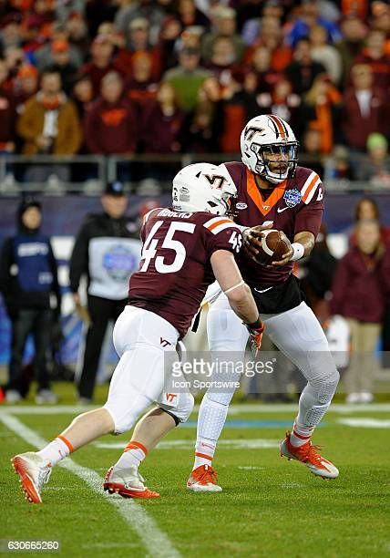 Virginia Tech Hokies quarterback Jerod Evans fakes a hand off to Virginia Tech Hokies fullback Sam Rogers during the first quarter of the Belk Bowl...