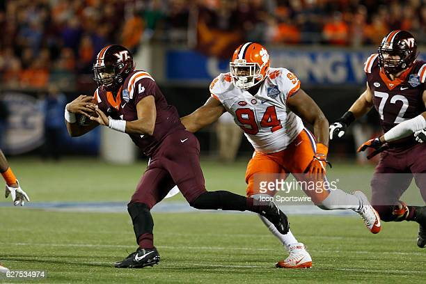 Virginia Tech Hokies quarterback Jerod Evans runs the ball as he tries to avoid being tackled by Clemson Tigers defensive tackle Carlos Watkins in...