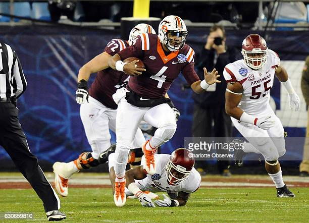 Virginia Tech quarterback Jerod Evans finds running room against Arkansas during the first half of the Belk Bowl at Bank of America Stadium in...