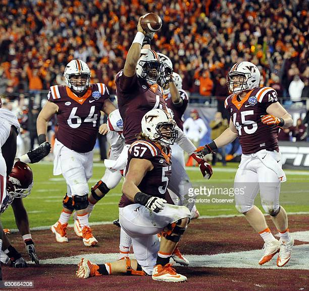Virginia Tech quarterback Jerod Evans holds the ball up after scoring the final touchdown against Arkansas in the Belk Bowl at Bank of America...