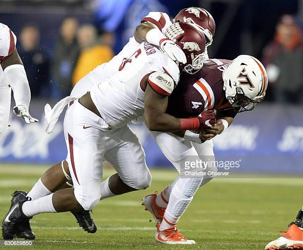 Virginia Tech quarterback Jerod Evans is brought down by Arkansas defensive lineman JaMichael Winston during the first half of the Belk Bowl at Bank...