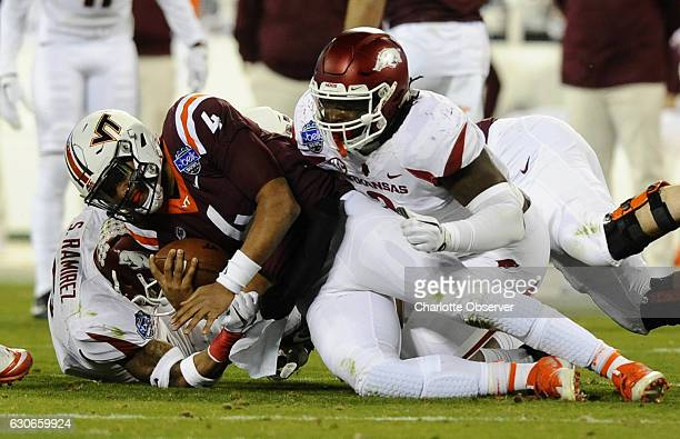 Virginia Tech quarterback Jerod Evans is brought down by Arkansas defensive back Santos Ramirez and defensive lineman McTelvin Agim in the first half...