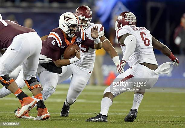 Virginia Tech quarterback Jerod Evans looks for running room against Arkansas defensive lineman JaMichael Winston in the first half of the Belk Bowl...