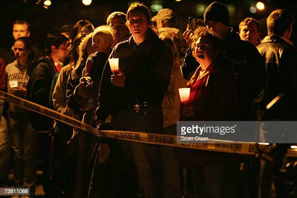 Virginia Tech student their fiends and families stand behind crime scene tape which surrounds the engineering building where at 30 students were...