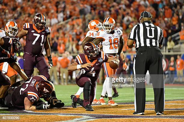 Virginia Tech University quarterback Jerod Evans gives the ball to the official after scoring a touchdown during the ACC Championship football game...
