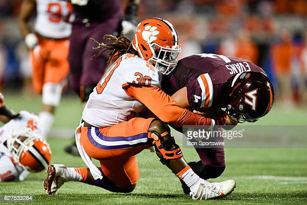Virginia Tech University quarterback Jerod Evans is tackled by Clemson University linebacker Jalen Williams during the ACC Championship football game...