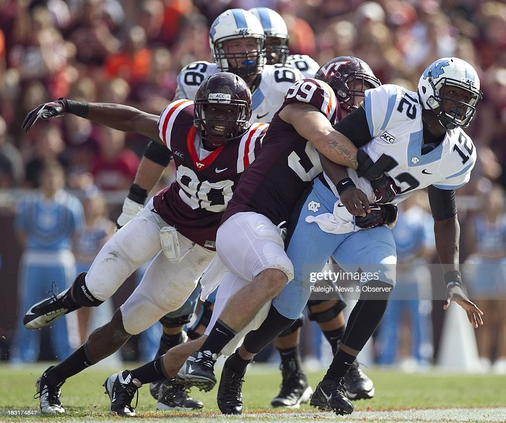 Virginia Tech's James Gayle (99) and Dadi Nicolas (90) drop North Carolina quarterback Marquise Williams (12), after he released a pass to Kris Francis in the fourth quarter at Lane Stadium in Blacksburg, Virginia, Saturday, October 5, 2013.