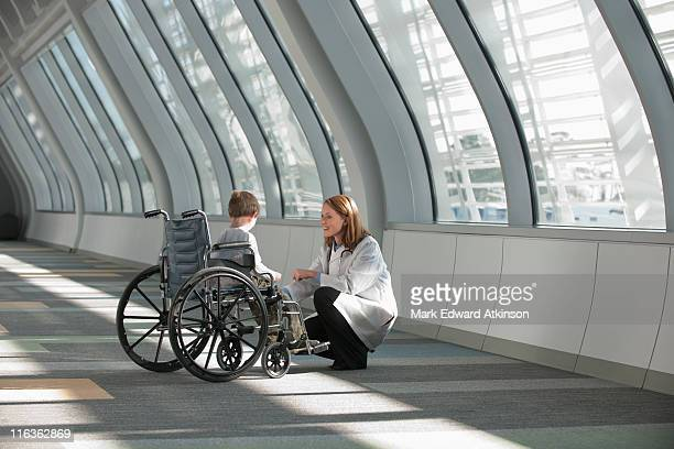 USA, Virginia, Virginia Beach, female doctor talking to boy (6-7) in wheelchair