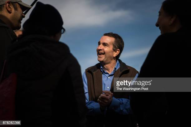 Virginia's Democratic gubernatorial candidate Ralph Northam shares a laugh with people during a campaign stop at Burke Farmer's Market on Saturday...