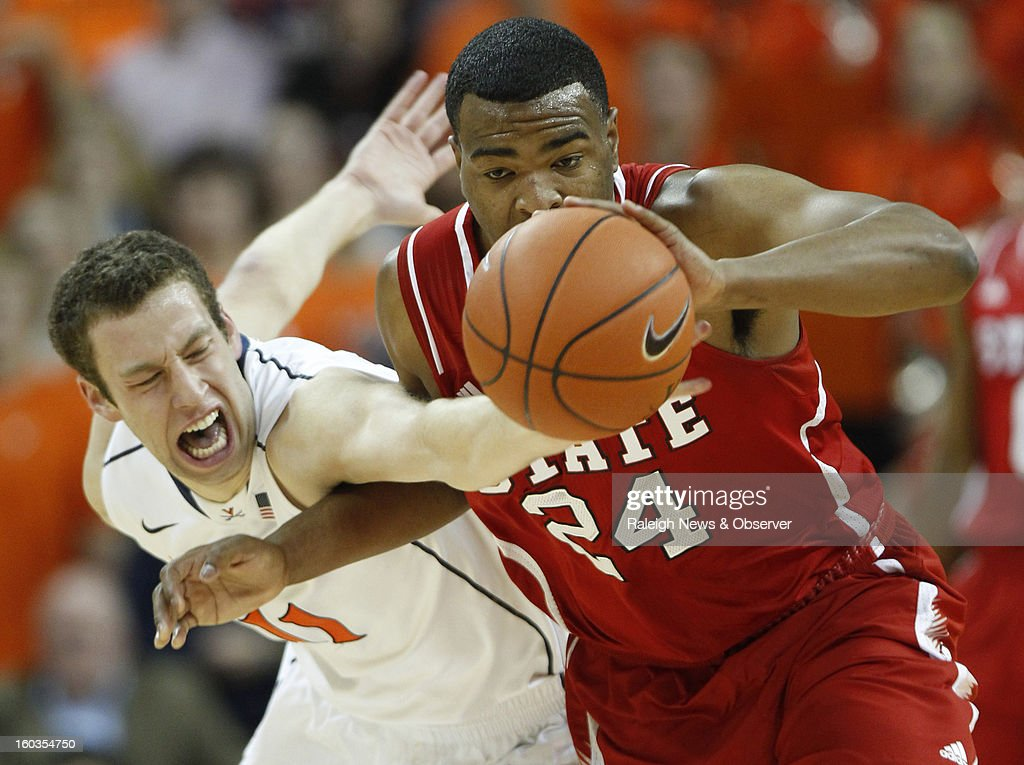 Virginia's Evan Nolte (11) fouls N.C. State's T.J. Warren (24) while competing for a loose ball during the first half at John Paul Jones Arena in Charlottesville, Virginia, Tuesday, January 29, 2013. The Virginia Cavaliers defeated the N.C. State Wolfpack, 58-55.