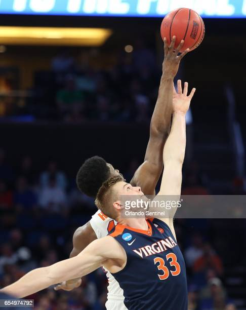 Virginia's Jack Salt and Florida's Kevarrius Hayes tip off during the second round of the NCAA Tournament at the Amway Center in Orlando Fla on...
