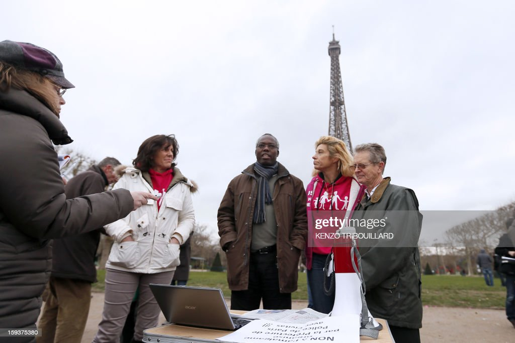 Virginie Tellene (2ndR), known as 'Frigide Barjot' speaks with militants against the same-sex marriage (Mariage pour tous), on January 12, 2013, at the Champs de Mars in front of the Eiffel Tower in Paris, on the eve of a national protest against the same-sex marriage. AFP PHOTO / KENZO TRIBOUILLARD