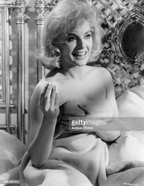 Virna Lisi covers herself with a blanket in a scene from the film 'How To Murder Your Wife' 1965