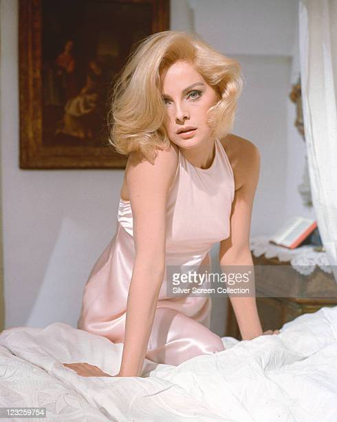 Virna Lisi Italian actress wearing a pink dress with her right knee raised up onto the bed on which she is leaning circa 1960