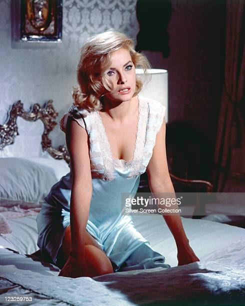 Virna Lisi Italian actress wearing blue silk nightdress with white lace trim as she kneels on a bed circa 1960