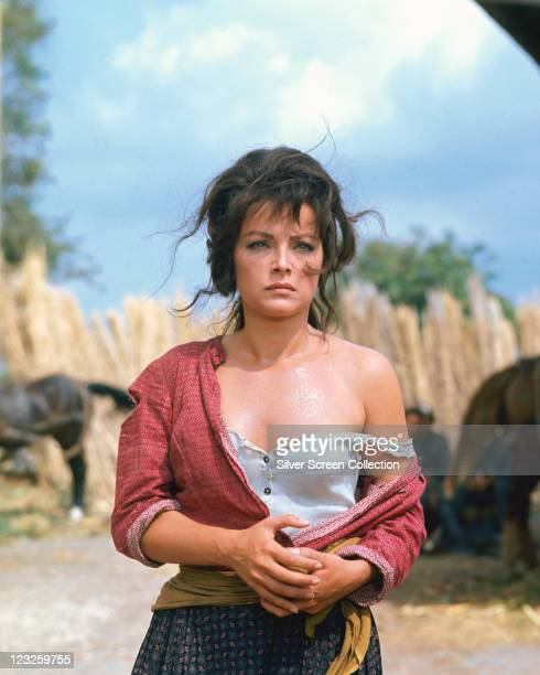 Virna Lisi Italian actress with a mournful expression on her face wearing a red cardigan which has slipped down to expose her left shoulder in a...