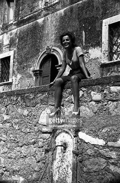 'Virna Lisi sits on the edge of a stone wall in Piazza Santa Vittoria above a standpipe coming out of the wall the Italian actress dressed in...