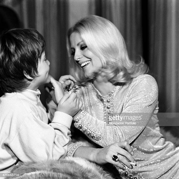 'Virna Lisi takes a break from an interview to play with her son Corradino holding a rosemary twig just found in the kitchen the Italian actress who...
