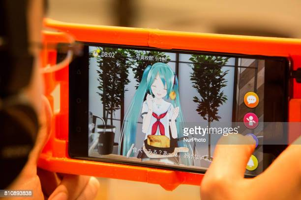 Virtual idol Hatsune Miku greets anime fan in a smart phone equipped with augmented reality application during an event in Sendai Japan on July 8...