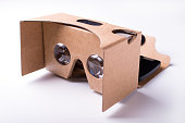DIY virtual reality headset. assembled from pre-cut cardboard and lenses. isolated over a white background with a smartphone attached.