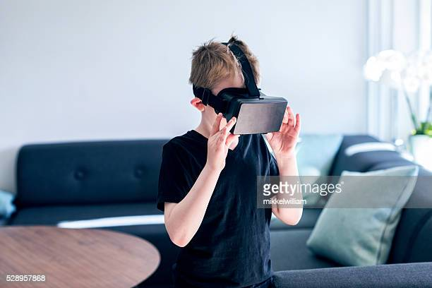 Virtual reality glasses are adjusted by a boy