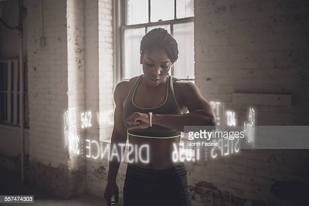Virtual words circling Black athlete checking fitness tracker