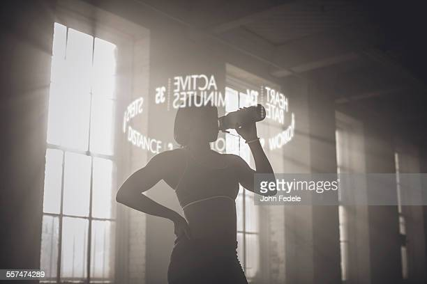 Virtual words circling Black athlete drinking from bottle
