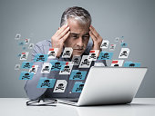 Businessman working with a computer full of viruses, infected files and malwares: he is frustrated with head in hands