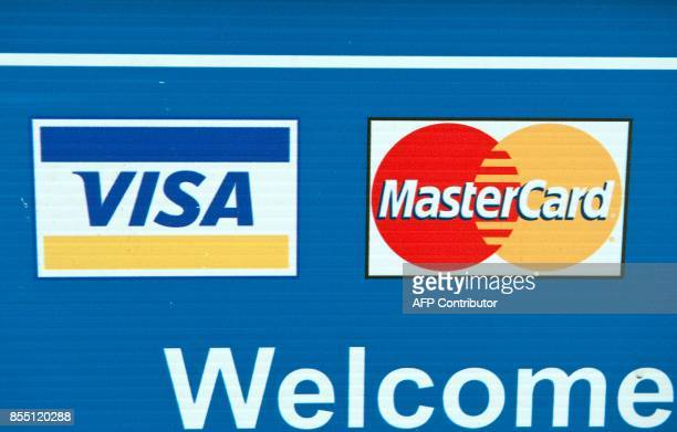 Visa and MasterCard credit card logos are seen on a sign in Washington on March 30 2012 Credit card giants Visa and MasterCard were scrambling to...