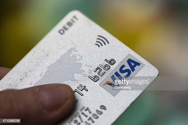 Visa Inc and contactless payment logos sit on a debit card in this arranged photograph in London UK on Friday May 22 2015 Credit and debit cards that...