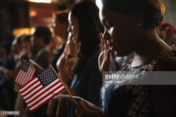Vishaun Lawrence of Jamaica takes an oath of citizenship during a naturalization ceremony at the Chicago Cultural Center on July 3 2013 in Chicago...