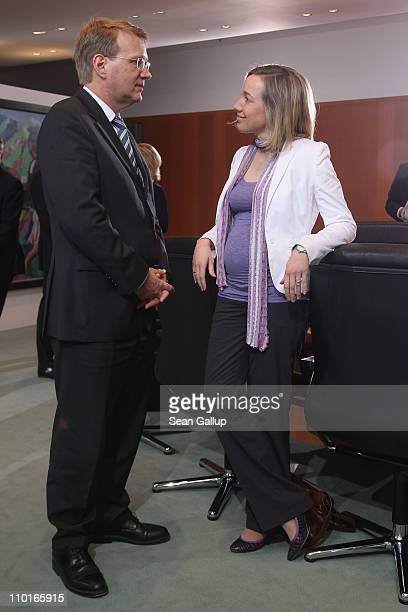 A visibly pregnant German Family Minister Kristina Schroeder speaks with Minister of the Chancellery Ronald Pofalla prior to the weekly German...