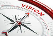 Arrow of a compass is pointing vision text on the compass. Arrow , vision text and the frame of compass are metallic red in color. White background. Horizontal composition with copy space. Vision conc