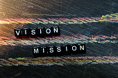 Vision Mission on wooden blocks. Cross processed image with blackboard background. Inspiration, education and motivation concepts