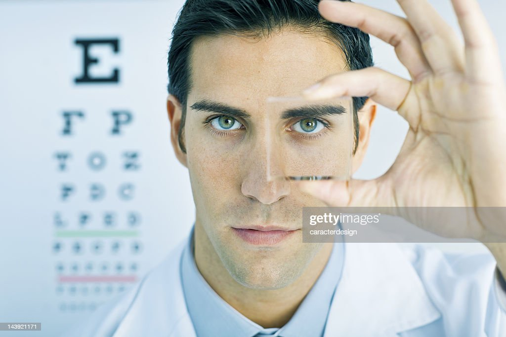 Vision: optometrist looking through a lens : Stock Photo
