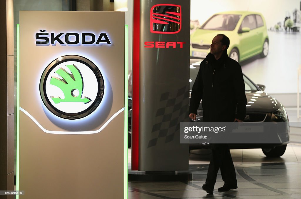 A visiotr walks past the logos of Skoda and Seat at a Volkswagen Group showroom on January 14, 2013 in Berlin, Germany. Volkswagen Group, which includes the VW, Audi, Porsche, Skoda, SEAT, Bentley and Bugatti brands, delivered a record 9.07 million cars to customers in 2012. Rising sales in the Americas and Asia helped to offset a drop in sales in western Europe.