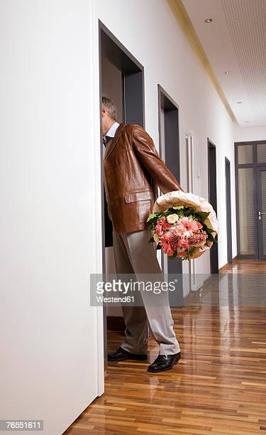 Man holding bouquet entering in to room