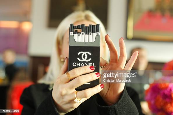 A visiter takes a photo by using a smartphone with a Chanel cover during the Thomas Sabo Press Cocktail event on January 20 2016 in Berlin Germany