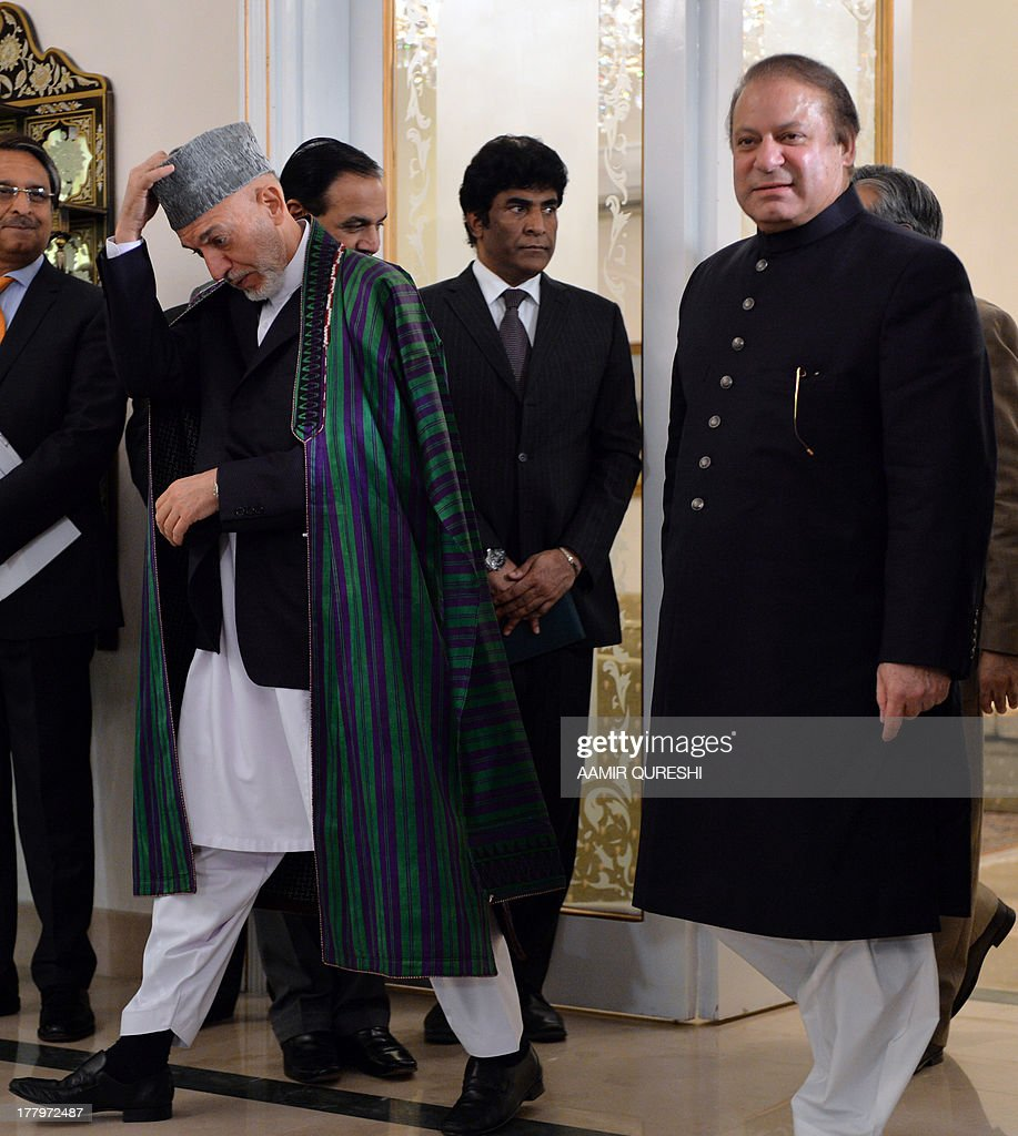 Visiting Afghan President Hamid Karzai (L) adjusts his cap as he arrives with Pakistani Prime Minister Nawaz Sharif (R) for a press conference at The Prime Minister's House in Islamabad on August 26, 2013. Karzai asked Pakistan to help arrange peace talks between his government and the Taliban, and demanded a joint campaign against extremism in both countries. The visit marks Karzai's first talks with newly elected Prime Minister Nawaz Sharif despite a history of stormy relations that have hampered efforts to end 12 years of war in Afghanistan.