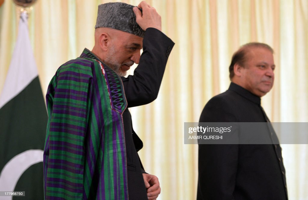 Visiting Afghan President Hamid Karzai (L) is flanked by Pakistani Prime Minister Nawaz Sharif as he adjusts his cap upon his arrival at The Prime Ministers House in Islamabad on August 26, 2013. Karzai asked Pakistan on August 26 to help arrange peace talks between his government and the Taliban, and demanded a joint campaign against extremism in both countries. The visit marks Karzai's first talks with newly elected Prime Minister Nawaz Sharif despite a history of stormy relations that have hampered efforts to end 12 years of war in Afghanistan.