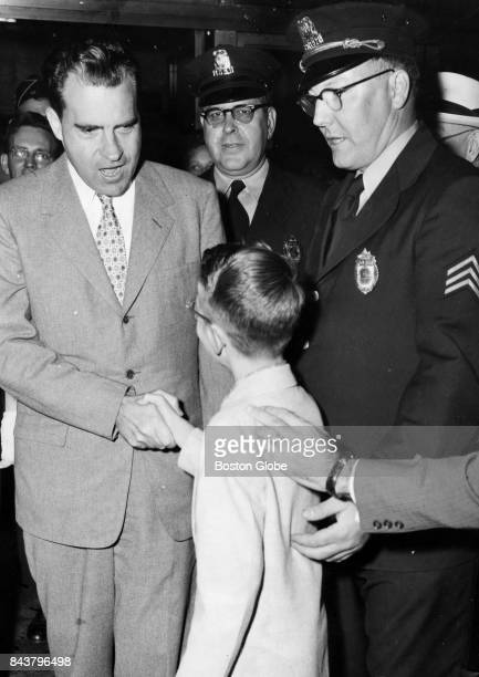Visiting Boston from Louisiana Charles J Perilloux of Baton Rouge shakes hands with VicePresident Richard M Nixon on Aug 28 1955 With them is Police...
