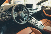 Visiting car dealership. Interior of modern automobile presented in dealership