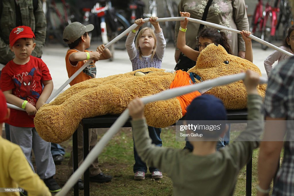 Visiting children hold high the intestine pulled from the belly of a giant teddy bear at the Teddy Bear Clinic at Charite Hospital on May 8, 2013 in Berlin, Germany. Charite Hospital hosts the annual Teddy Bear Clinic days and invites children from Berlin day care centers to bring their injured teddy bears for fictitious examinations, x-rays, surgery and healing as a way for small children to become acquainted with a medical environment.