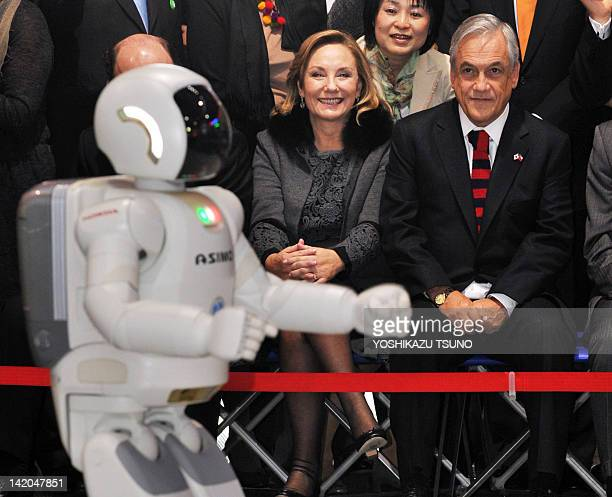 Visiting Chilean President Sebastian Pinera and his wife Cecilia Morel enjoy a demonstration of Honda's humanoid robot 'Asimo' at a science museum in...