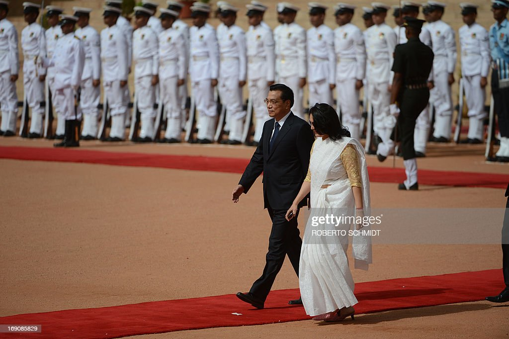 Visiting Chinese Premier Li Keqiang (C) is escorted by an official as he walks past the Indian Presidential guard during his official welcoming ceremony in New Delhi on May 20, 2013. Visiting Chinese Premier Li Keqiang has pledged to build up trust with India as he held talks with his counterpart Manmohan Singh in the wake of a flare-up of a border dispute.