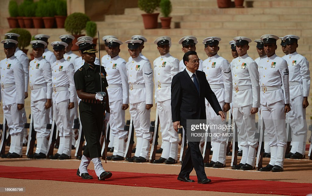 Visiting Chinese Premier Li Keqiang walks past the Indian Presidential guard during his official welcoming ceremony in New Delhi on 20 May 2013. Visiting Chinese Premier Li Keqiang has pledged to build up trust with India as he held talks with his counterpart Manmohan Singh in the wake of a flare-up of a border dispute.AFP PHOTO/ROBERTO SCHMIDT